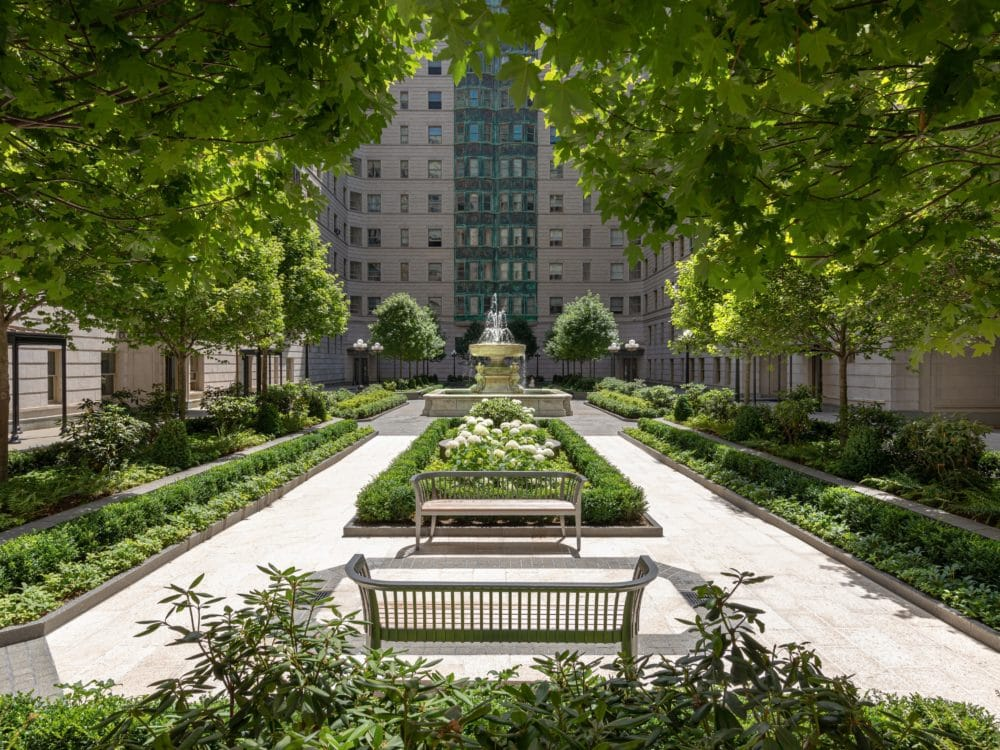 Courtyard at The Belnord apartments in New York City. Rectangular walkway with benches and greenery bordering both sides.