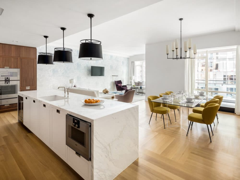 Kitchen and dining room at The Hayworth condos in NYC. White stone kitchen island, dining table with chairs & natural light.