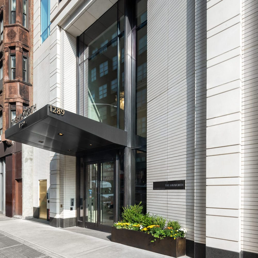 Daytime side view of The Hayworth entry in New York City. White walls, bronze double doors, potted bushes, and a dark canopy.