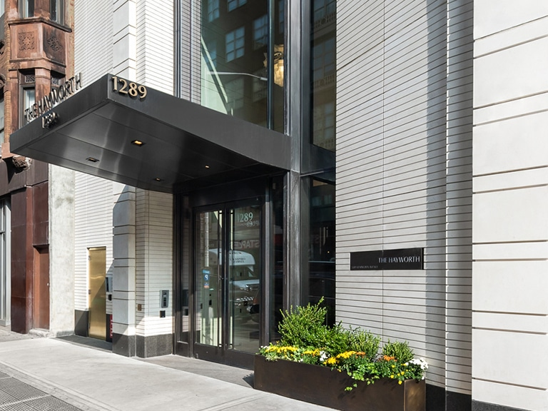 Side view of The Hayworth entry in New York City. White walls, bronze double doors, potted bushes, and a dark canopy.