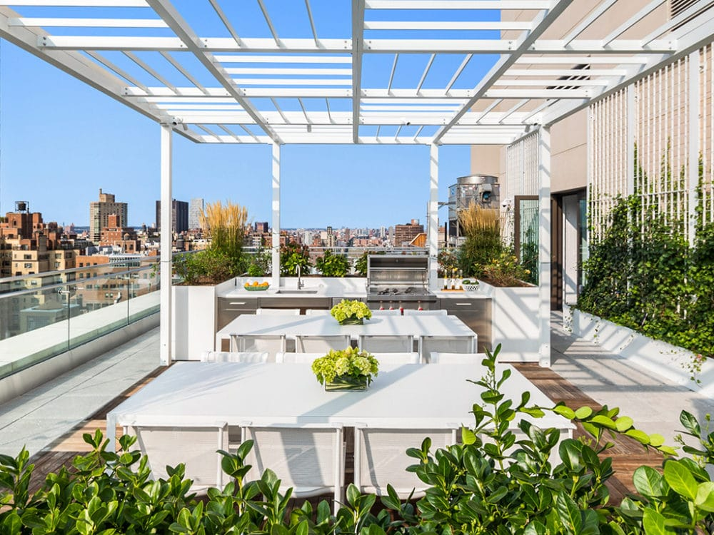 Rooftop deck at The Hayworth condos in NYC. Outdoor space with seating, a barbecue, potted plants and city views.