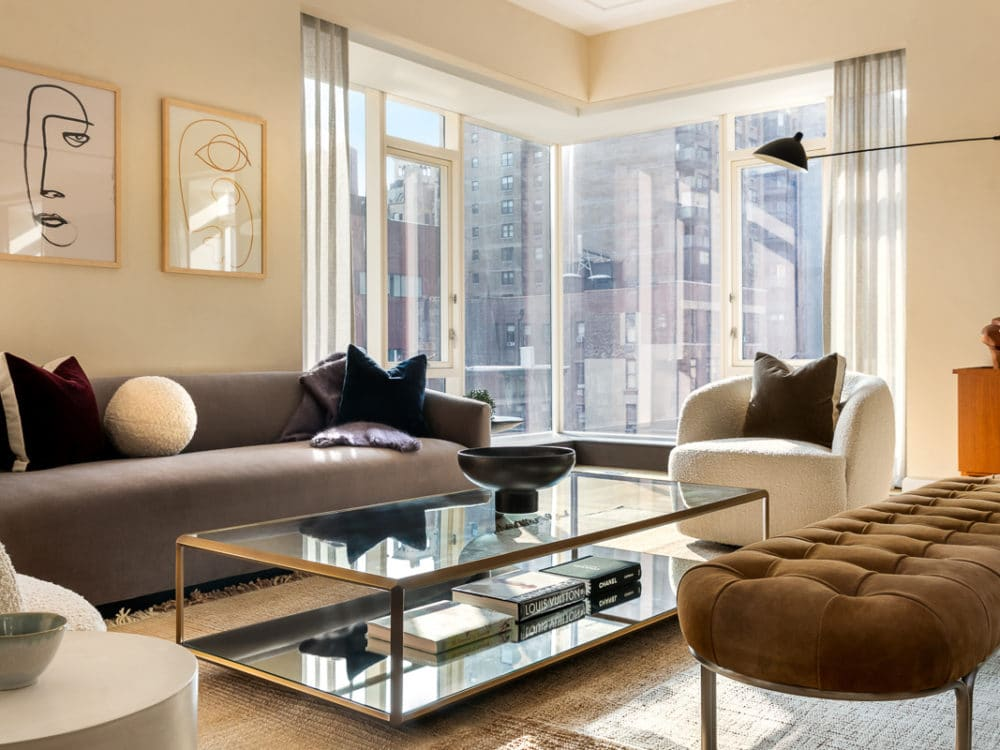 Living room in The Hayworth in New York City. Tall corner windows, art hanging on the walls and seating around a glass table.