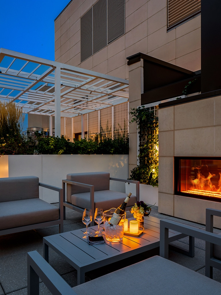 Rooftop patio at The Hayworth luxury condos in New York City. Four chairs and a table next to fireplace insert at night.