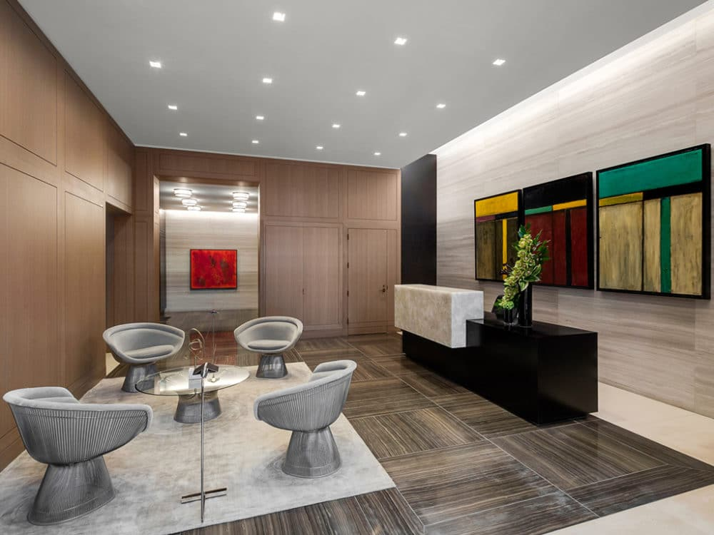 Lobby at The Hayworth condos in New York. Sitting area with 4 chairs, light brown walls, white ceilings and hung paintings.