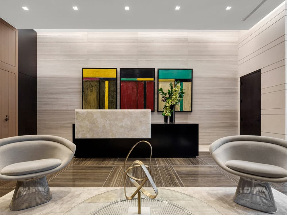 The Hayworth condos lobby in New York. Two round chairs, white walls with three paintings side by side behind front desk.