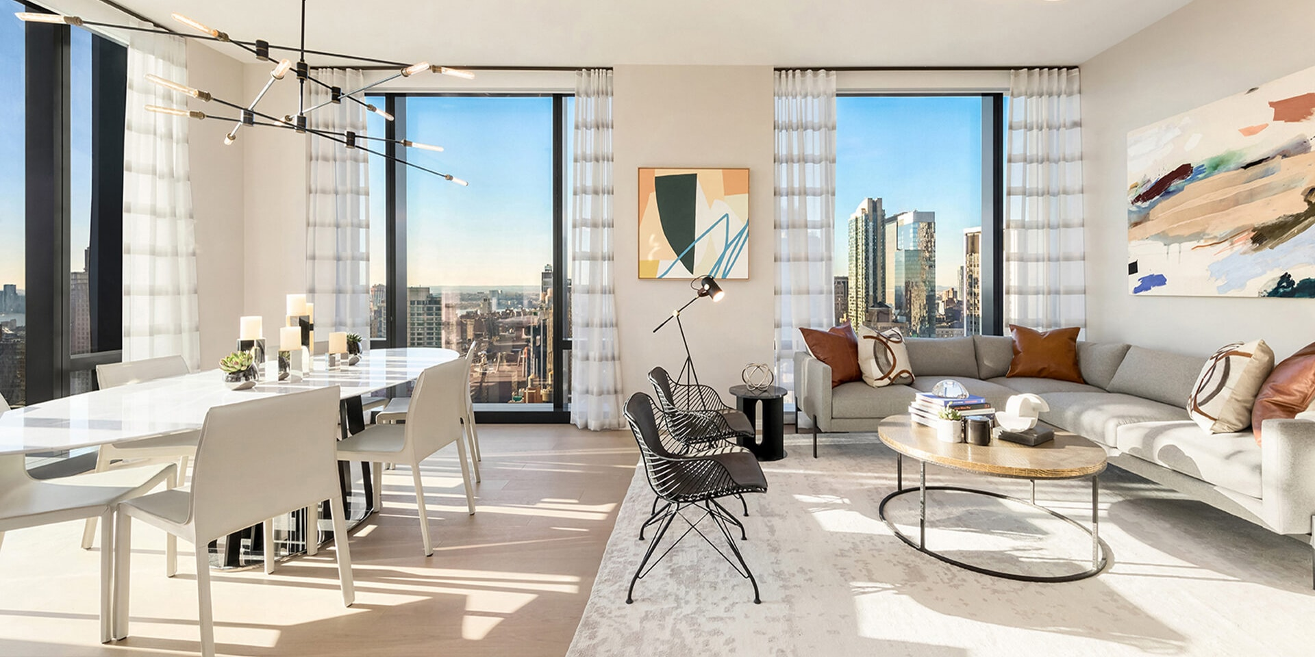 Open concept living and dining room at 277 Fifth Ave luxury condos in New York. White accents with furniture and city views.