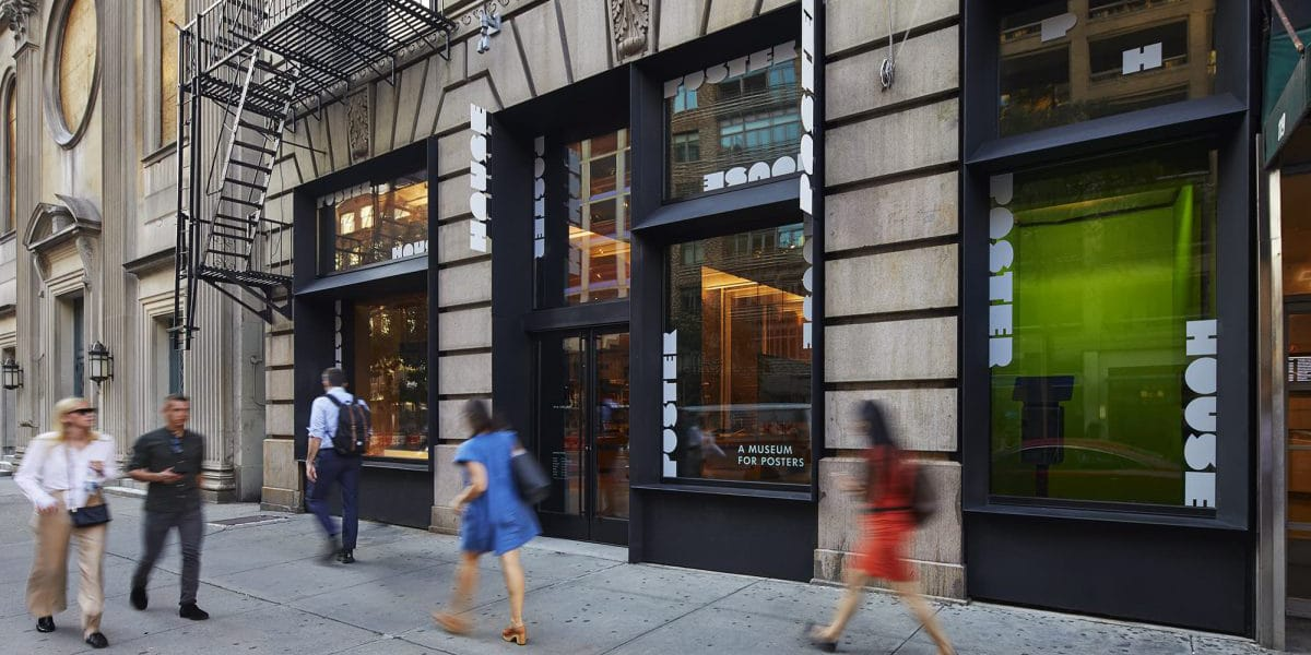 Street view of stone building in New York with black accents. People walking on the sidewalk during the day.