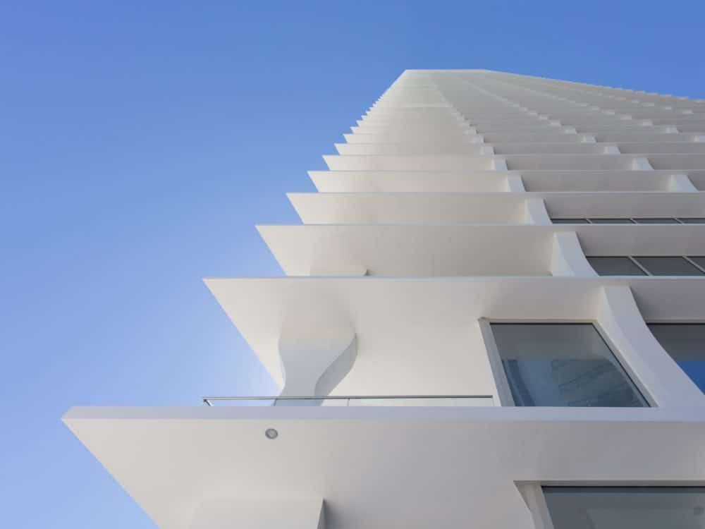 Exterior scale view of Jade Signature condominiums balconies with an oceanfront view. Decorative white walls and windows.