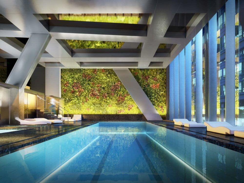 53 West 53 residence indoor pool located in New York City. Has white pillars, dark flooring and chairs.