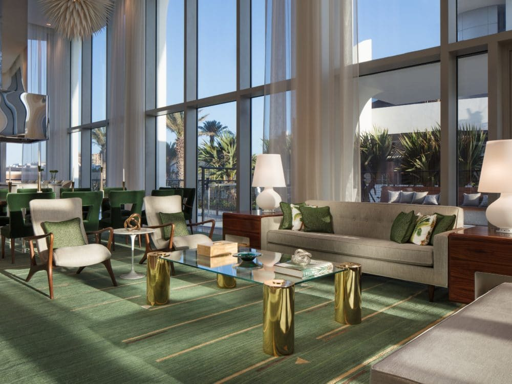 Interior view of Jade Signature residence club room with oceanfront view. Has a green rug and full lounging furniture.