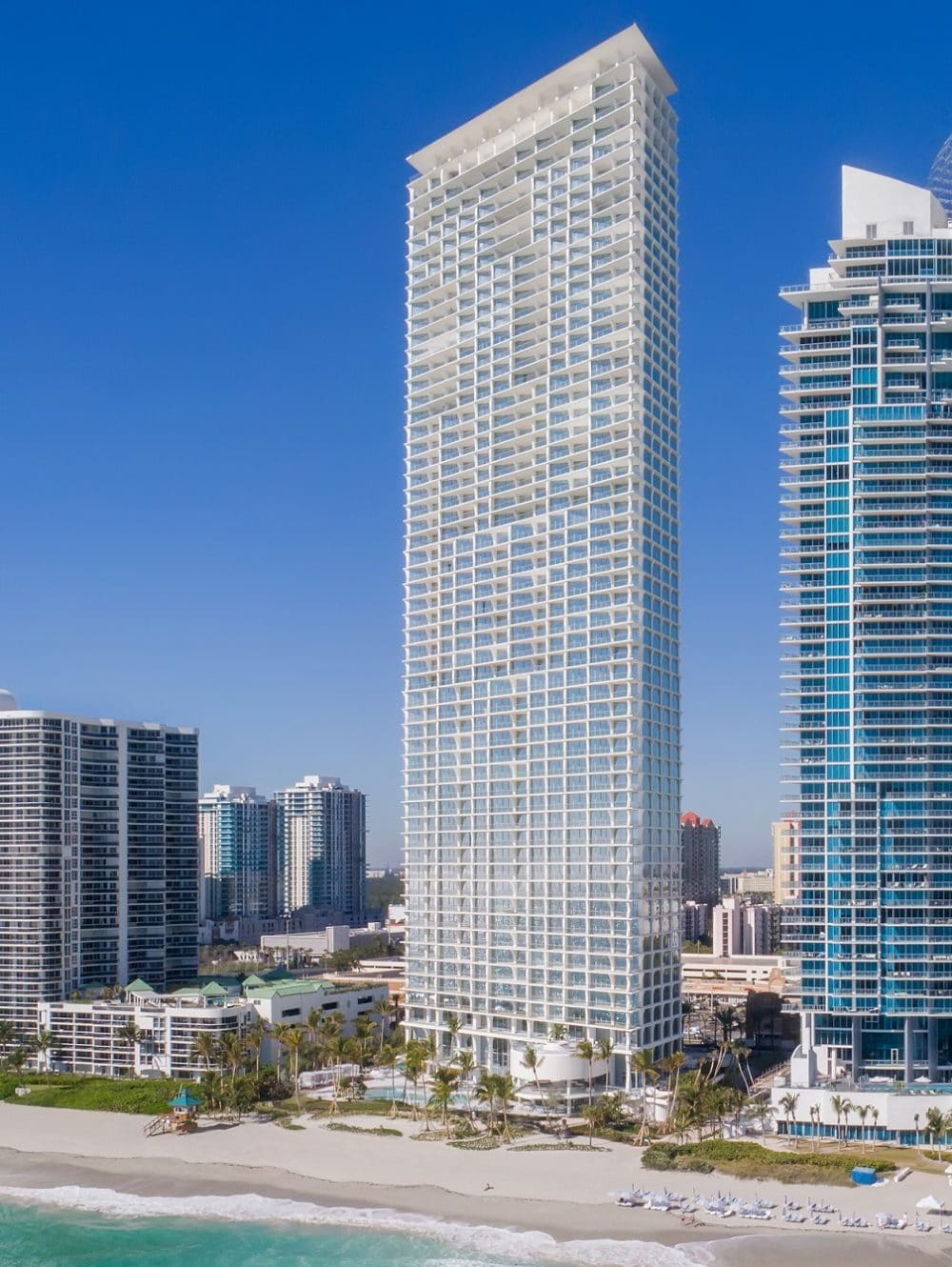 Exterior view of Jade Signature condominiums with oceanfront view. Has surrounding buildings in Sunny Isles.