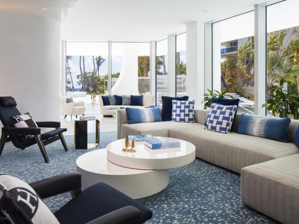 Interior view of Jade Signature residence entertainment lounge. Includes oceanfront window view and lounging furniture.