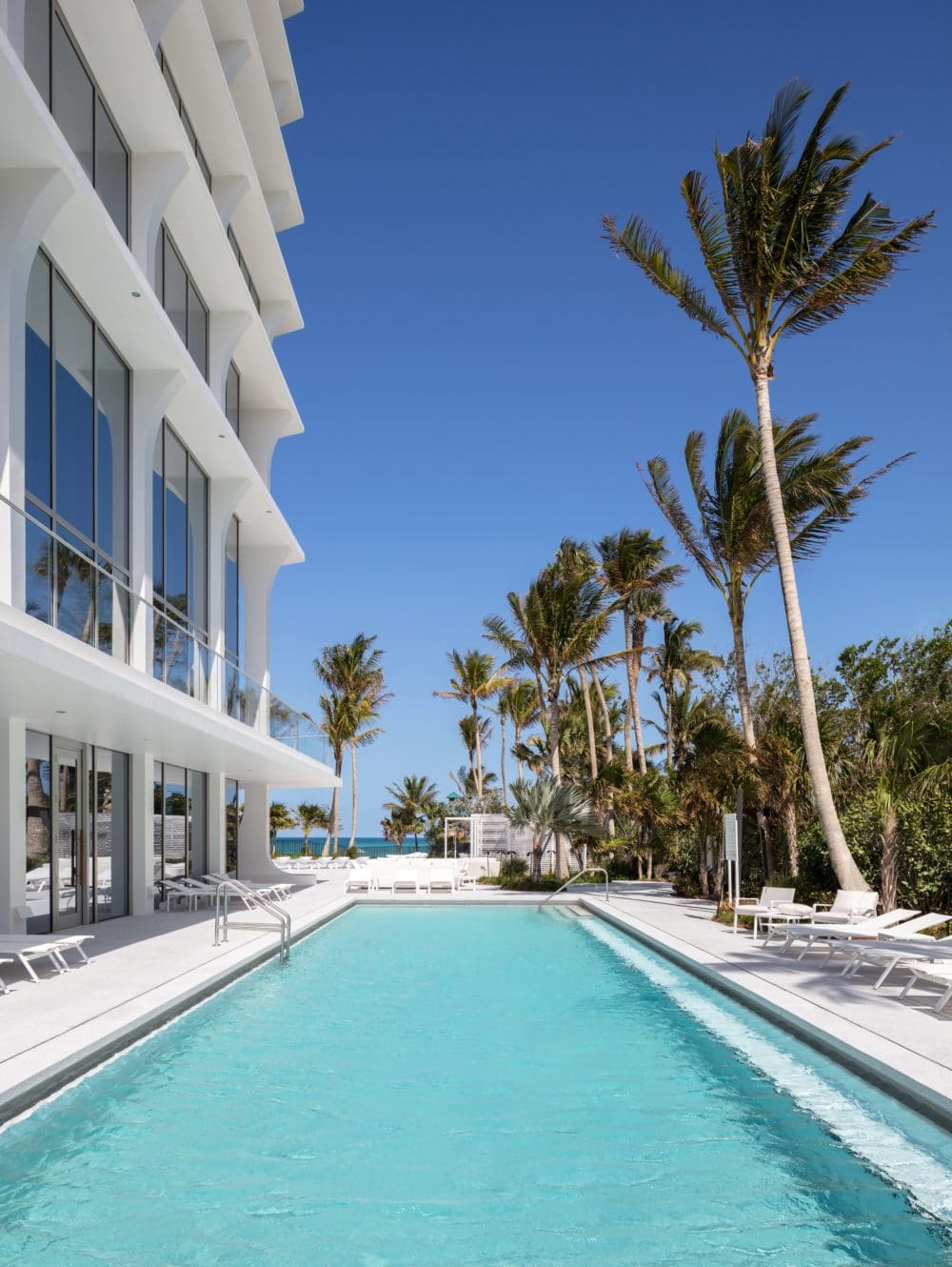Exterior view of Jade Signature condominiums outdoor pool with oceanfront view. Has lounge chairs and palm trees.