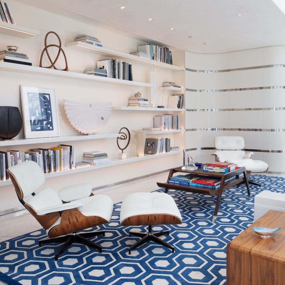 Interior view of Jade Signature residence library. Has white bookshelves, blue patterned rug, and lounge chairs.