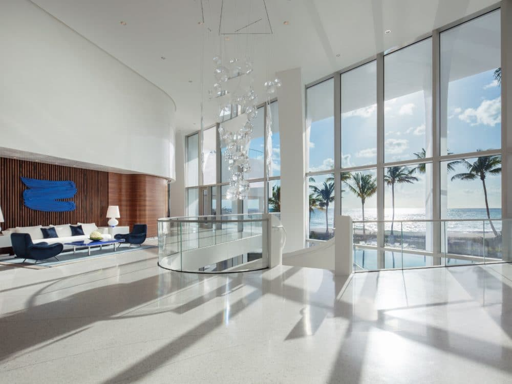 Interior view of Jade Signature residence lobby with tiled flooring and open windows. Has an oceanfront and palm tree view.