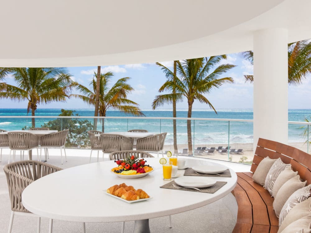 Exterior view of Jade Signature condominiums pavillion terrace. Has a table and chair set with an oceanfront view.