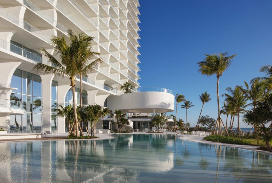 Exterior view of Jade Signature condominiums pool, bar and grill area. Has oceanfront view with palm trees surrounding.