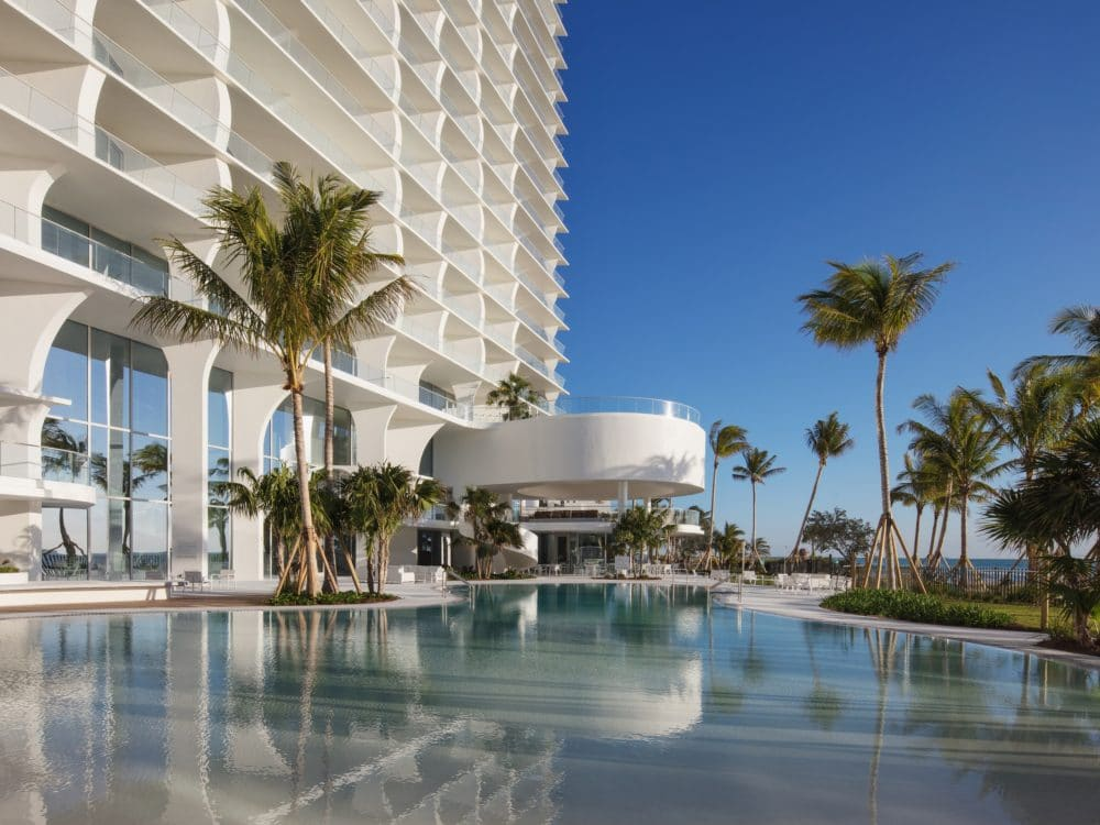 Exterior view of Jade Signature condominiums bar, grill and pool area. Has an oceanfront view and palm trees.