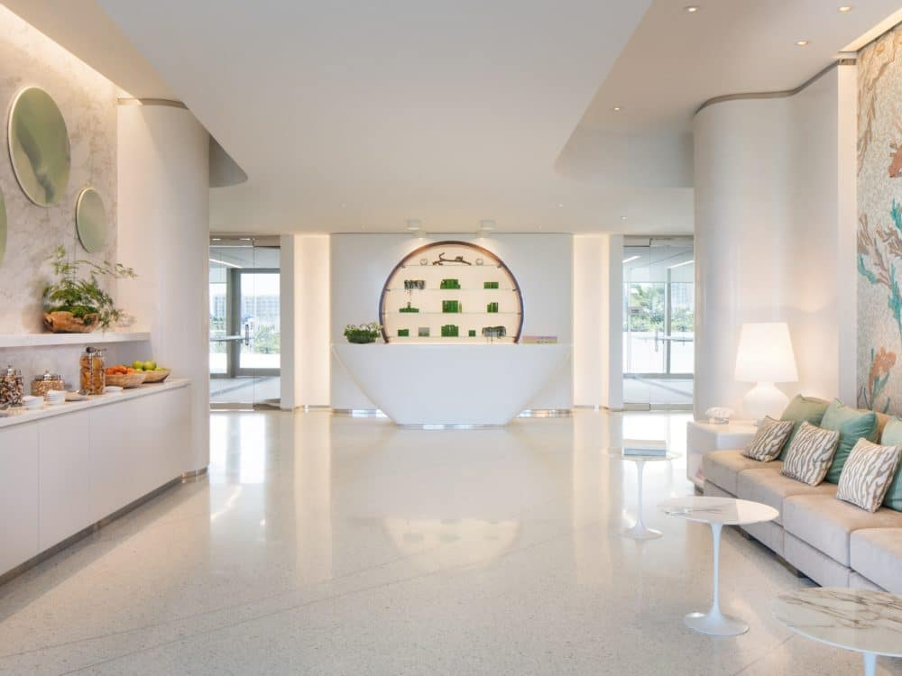 Interior view of Jade Signature residence spa reception area. Has waiting chairs with pillows and elegant white floors.