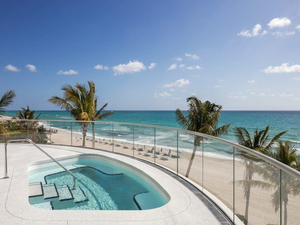 Exterior view of Jade Signature residence water terrace with oceanfront view. Has glass rail, palm trees and hot tub.