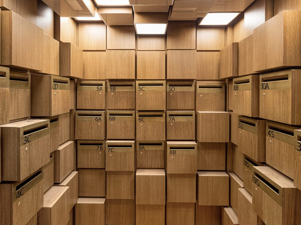 Jardim condo complex mail room in New York. Interior picture of sculpture designed mail room with offset brown mail boxes.