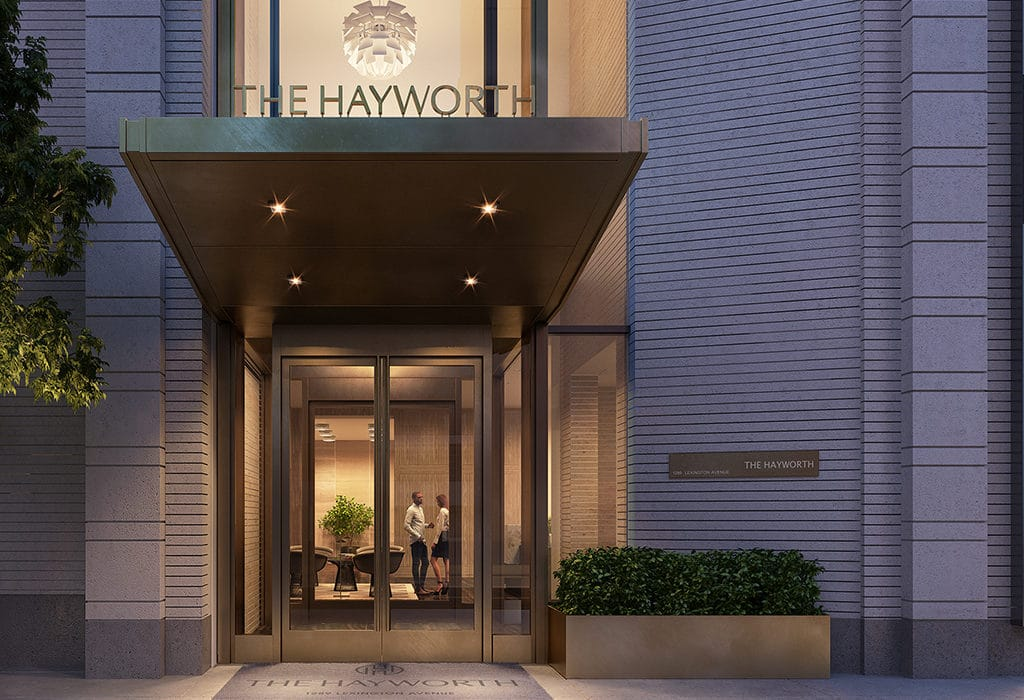 The Hayworth Condos entrance in New York City. Bronze double doors, potted bushes, and a well lit canopy cover.