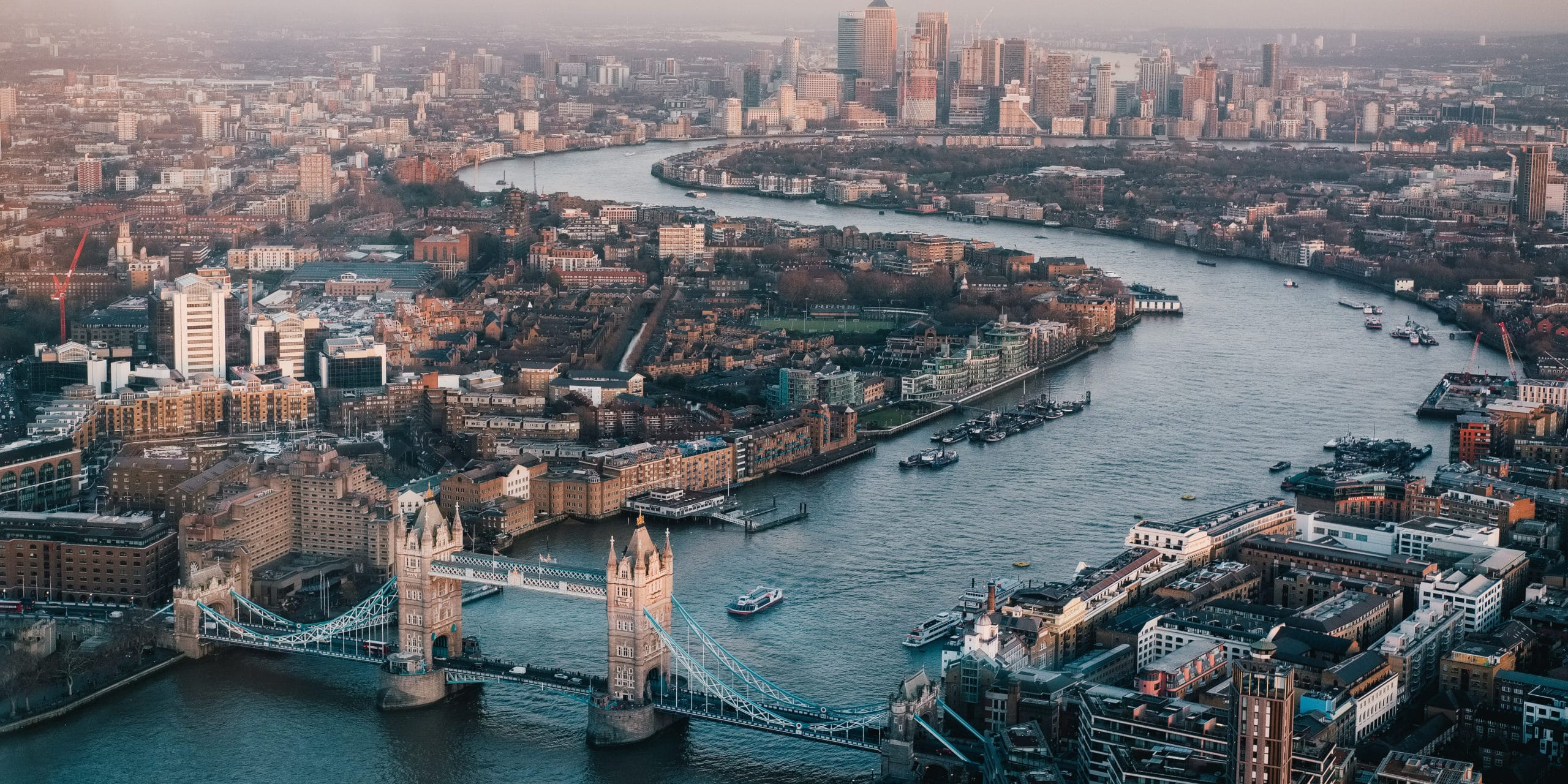 Aerial view of the River Thames winding through the city of London. City skyline with the Tower Bridge in the forefront.