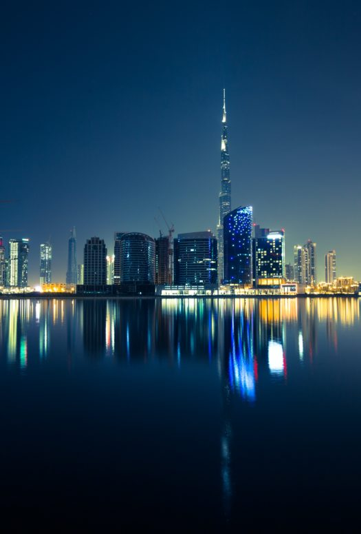 City skyline of Dubai at night. Picture taken from the water looking at the dark with with high rises along the waterfront.