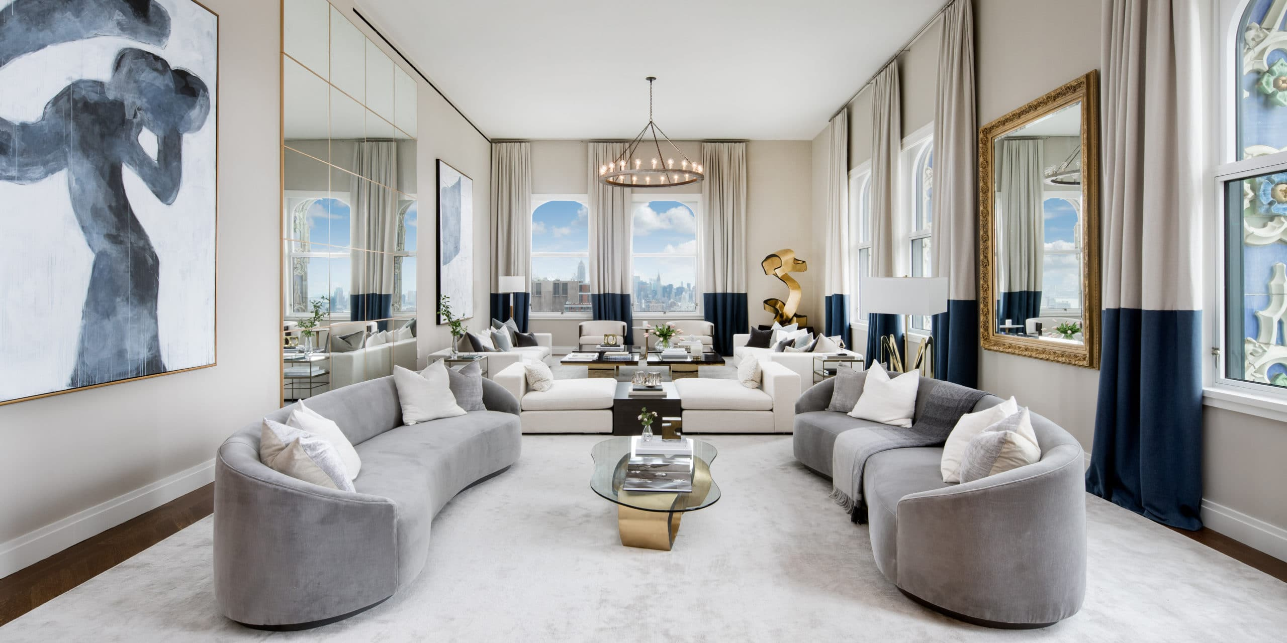 Living room at The Woolworth Tower luxury condos in NYC. High ceilings, off white walls, with curved couch and a painting.
