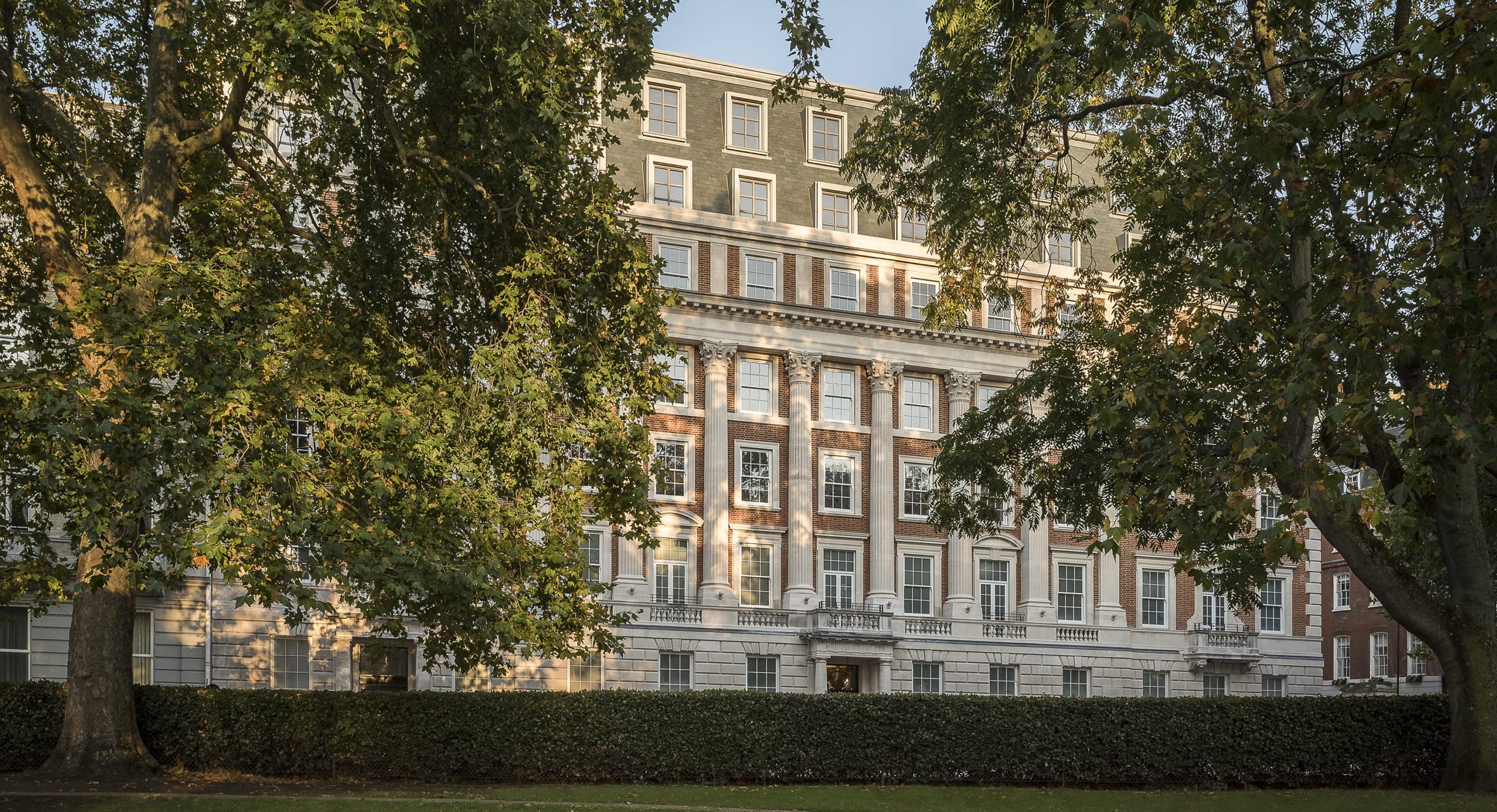 Exterior of 1 Grosvenor Square in London. Former US Embassy building framed by two trees with brick facade and white accents.