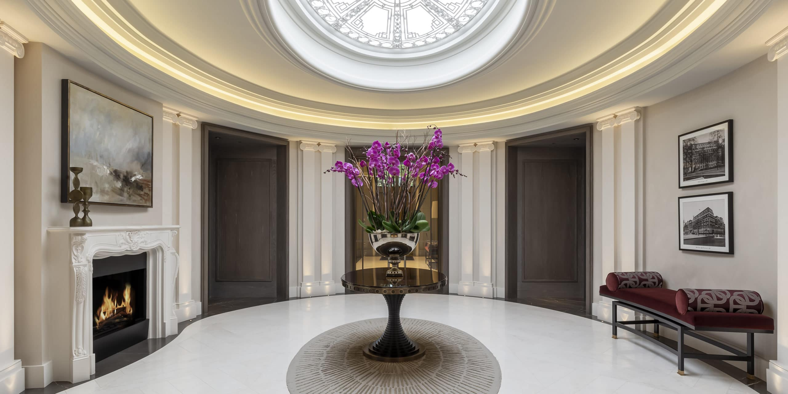 Oval room at 1 Grosvenor Square penthouse in London. Dome ceiling with natural light, white walls, & fireplace on left wall.