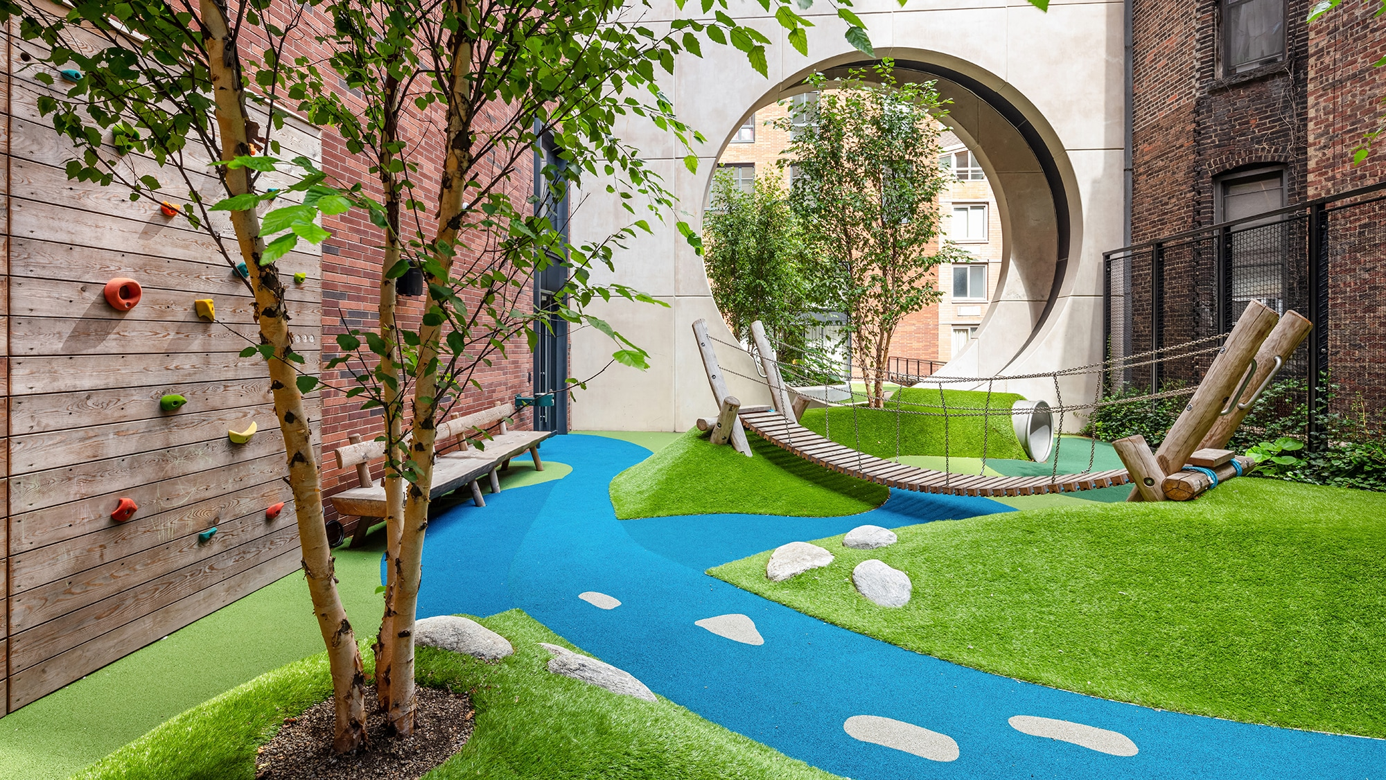 Kids playroom at The Kent condominiums in New York. Outdoor park theme with slide, turf floor, trees and a climbing wall.