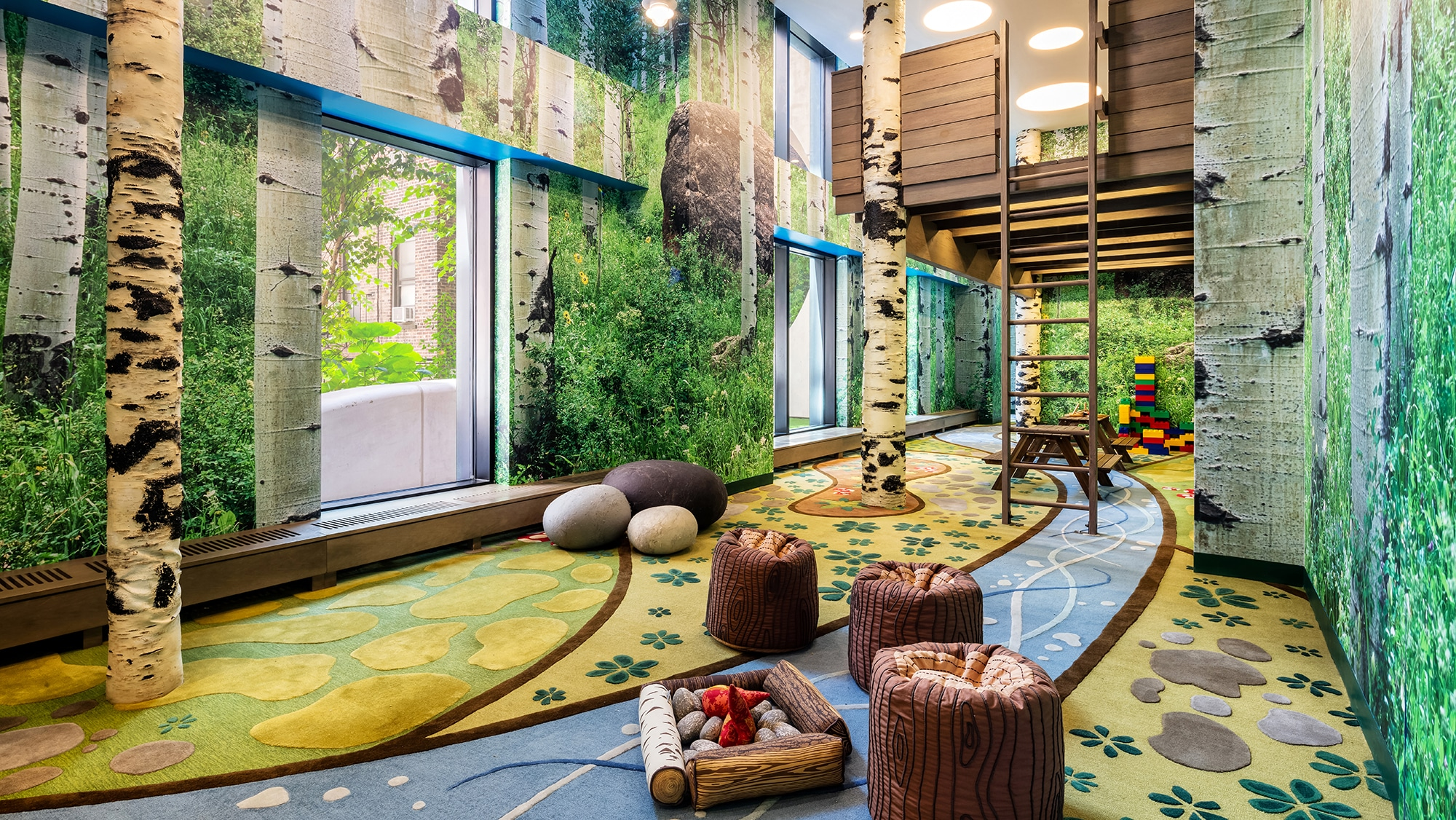 Kids playroom in The Kent Condos in NYC. Large room with forest themed wallpaper, a tree house, and sitting areas.