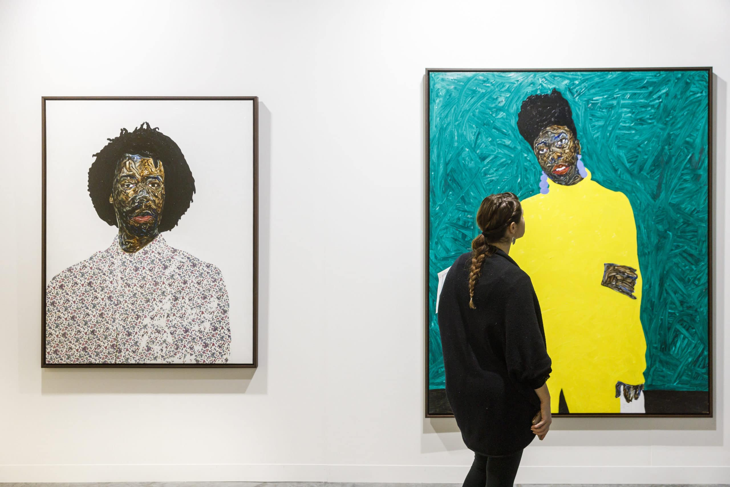 Closeup view of portrait paintings inside Art Basel. A woman is looking at a painting and has a white wall background.
