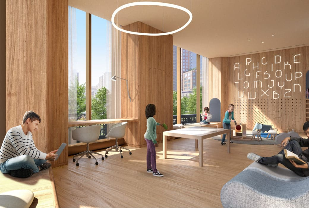 The playroom at The Xi luxury condos in NYC. Large room with chairs, couches, toys, and large windows with views.