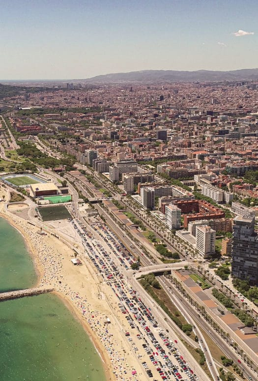 Aerial view of oceanfront properties in Barcelona. Has beachfront open space and tall buildings.