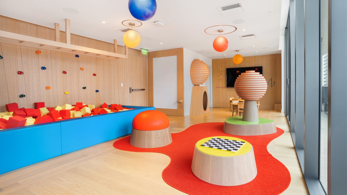 Kids playroom at Brickell Flatiron luxury condos in Miami. Natural wood floor and walls, a red carpet, a foam pit, and toys.