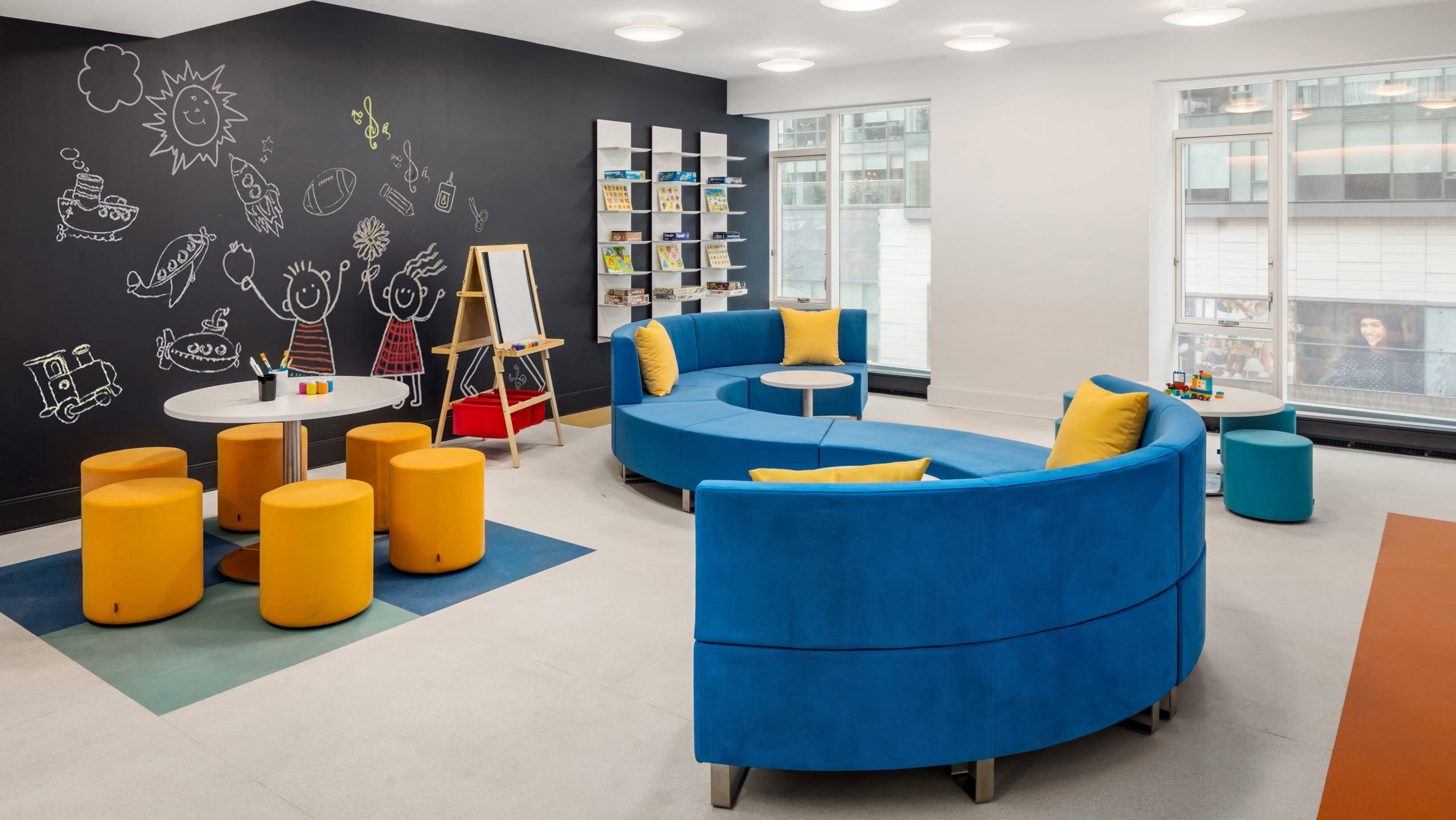"""Kid's playroom at The Hayworth condos in NYC. A large """"S"""" shaped couch, art supplies, and a black accent wall with a mural."""