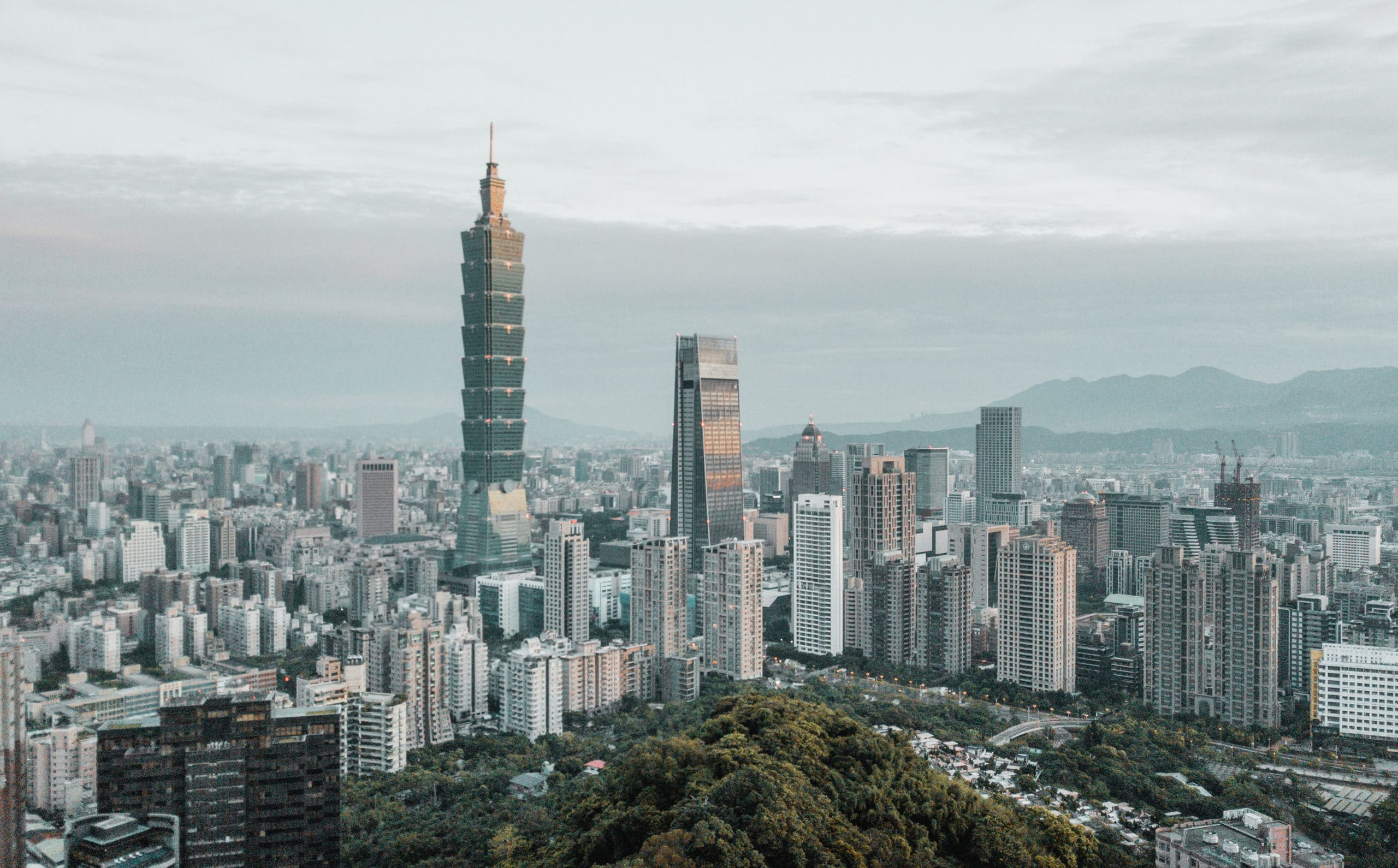 Exterior aerial view of Taipei, Taiwan with skyscrapers and surrounding city buildings.