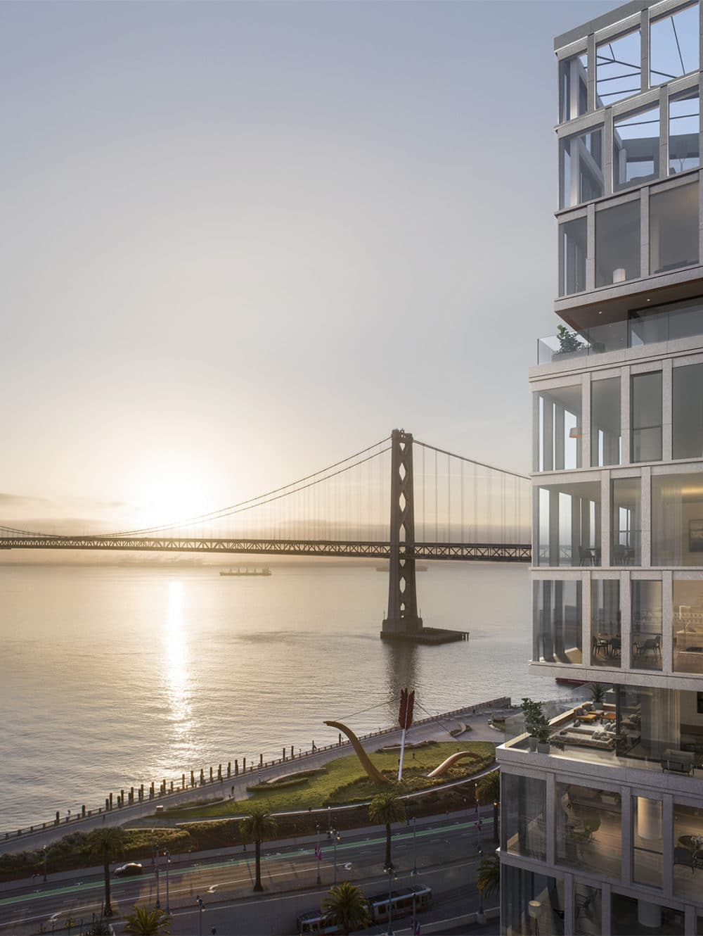 Birds-eye view of One Steuart Lane condos in SF. Sun reflecting off glass facade with Bay Bridge in the distance at sunrise.