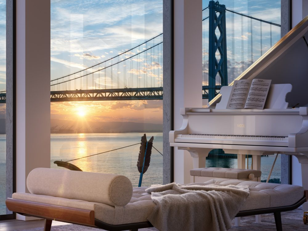 Close up of bench and white piano with a view of the sunrise behind the Bay Bridge at One Steuart Lane in San Francisco.