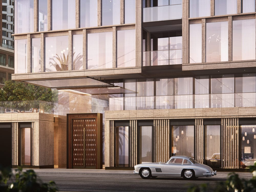 Entrance to One Steuart Lane condos in San Francisco. Street view of building with tall windows, large brown door, & balcony.