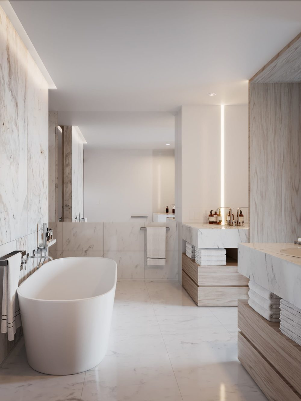 Master bathroom at One Steuart Lane in SF. Marble finishes & white floor with two vanities, standing shower, and soaking tub.