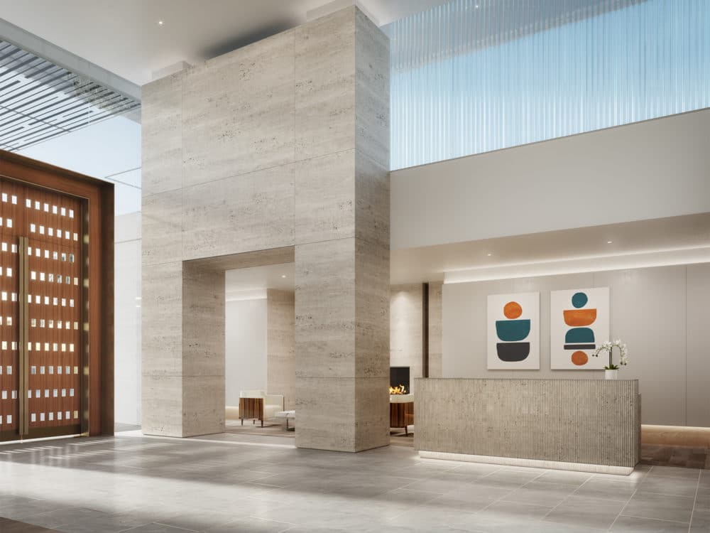 Lobby at One Steuart Lane condos in San Francisco. High ceilings with pillar walkway to seating area & light gray front desk.