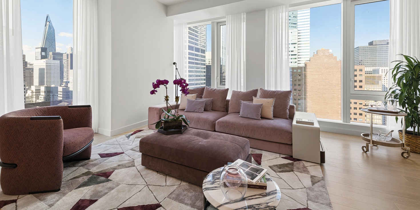 Living room at The Centrale condominium in New York. Marble floor with tall windows, couch, and chairs with city views.