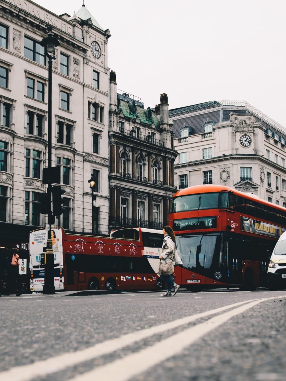 Street view of light brick buildings, cars and buses on the roads, and pedestrians crossing the street in London, England.