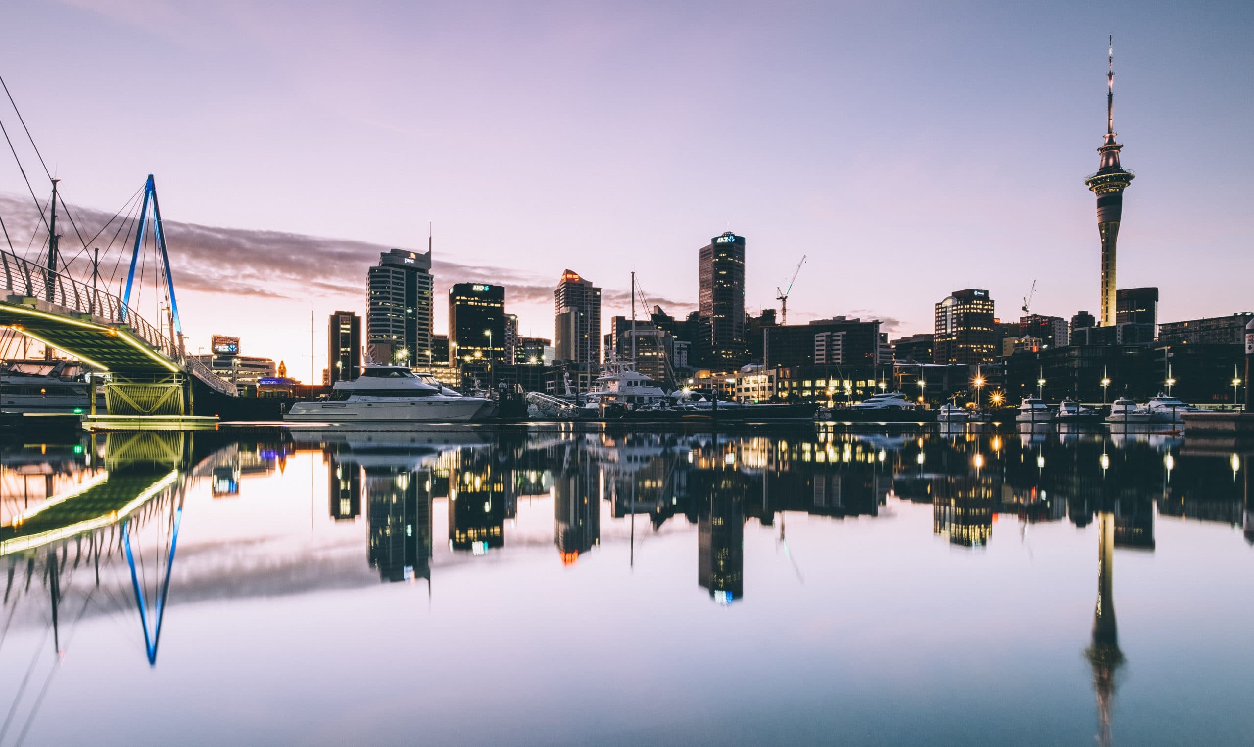Exterior view of Auckland, New Zealand with skyline buildings with waterfront view. Has a large glowing bridge and a sunset.