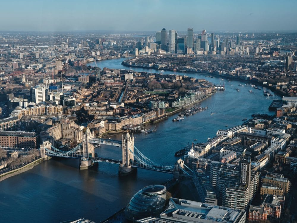 Aerial view of the River Thames winding through the city on London. Tower Bridge can be seen in the forefront of the photo.