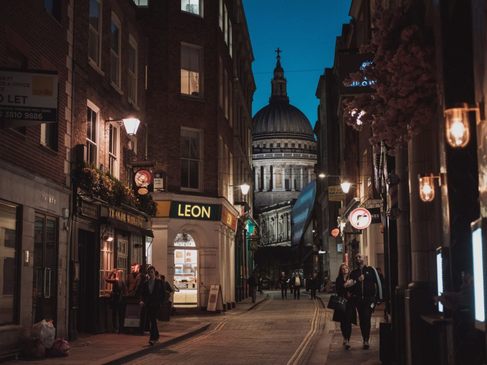 Photo of the streets of London at night. Lights are on, streets are empty and a few pedestrians are walking on the sidewalk.