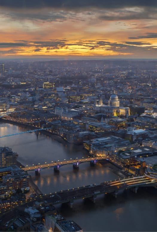 Aerial view London, England at dusk. Thames River running between the city with two bridges and the sunset in the distance.
